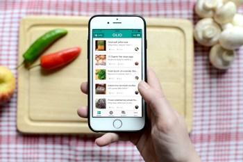 Smartphone med appen igång där olika produktval syns, hålls ovanför en skärbräda i trä.