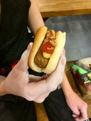 Barnhand håller i en halvt uppäten varmkov med bröd, senap, ketchup och rostad lök.