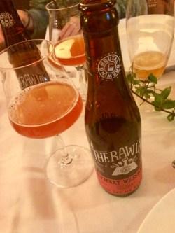 Brun glasflaska till höger om ett ölglas med lite rosafärgad öl i. Står på vit linneduk