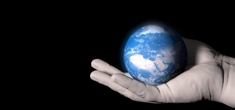 Planeten jorden som en boll i en persons öppna högerhand från höger in i bild mot en svart bakgrund