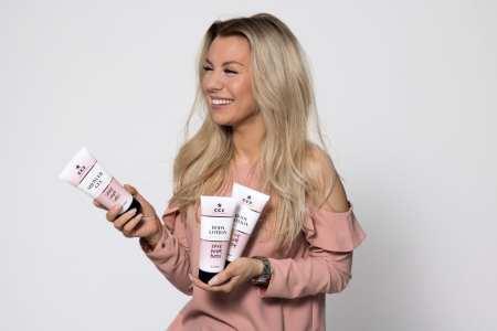 Therése Lindgren, vit ung kvinna med långt blont hår, sedd från sidan, skrattar och håller två tubflaskor i vänster hand och en i höger. Vita med rosa detaljer av märket CCS Love your body