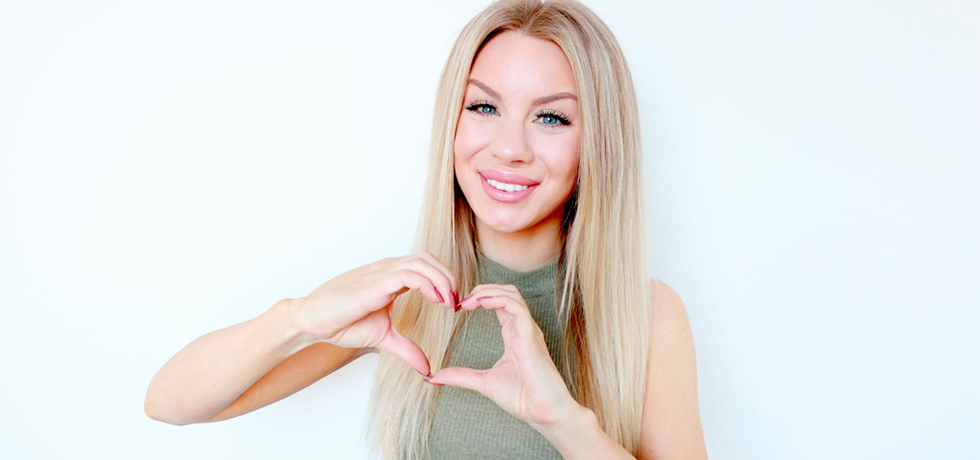 Therése Lindgren, vit, ung kvinna med långt, rakt blont hår, ler in i kameran och gör ett hjärta med händerna framför sig.