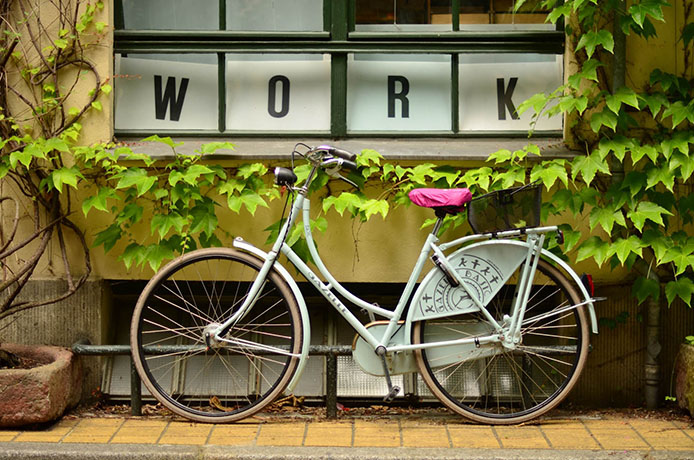 Vit cykel med rosa sadelskydd lutad mot vägg med klängväxter. Ordet WORK i bakgrunden