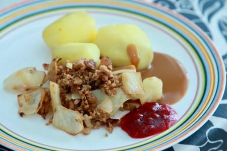 Kålpudding med kokt potatis, brunsås och lingon på en tallrik med ränder längst ut