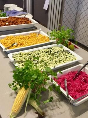 Uppläggningsfat på rad med hackade grönsaker och färs