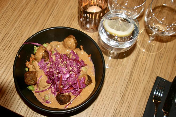 Svart skål med kikärtsbullar, picklade rödlök och jordnötssås sett uppifrån, ovanför glas med vetten och citronskiva samt ett tänt värmeljus