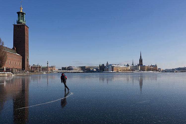 En skridskoåkare på blank is på Riddarfjärden i Stockholm, till vänster syns Stockholms Stadshus.