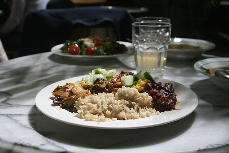 Tallrikar med ris och grytor på, två glad med vatten står mellan