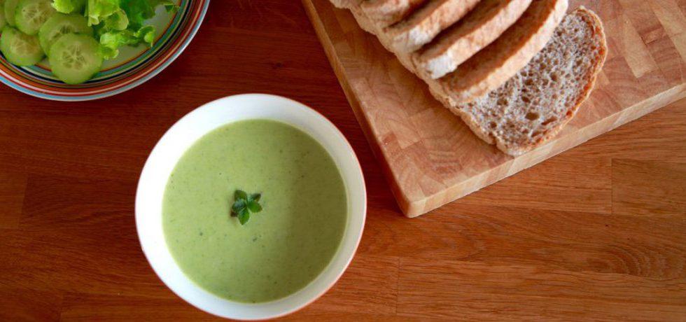 Broccolisoppa i skål uppifrån, till höger en skärbräda med skivat, mjukt bröd, till vänster sallad och skivad gurka
