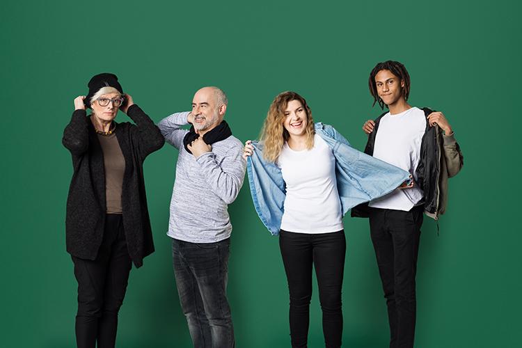 Fyra personer mot en grön vägg som tar på sig en skjorta, mössa och halsduk