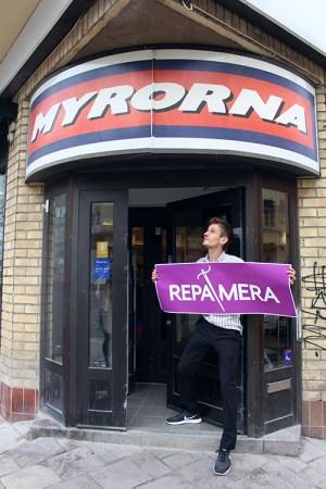 En man håller i en lila skylt med texten REPAMERA i vitt. Står i en dörröppning, ovanför hänger skylt med Myrornas logo på