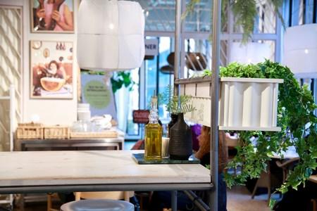 Ljusa bord med vita lampor över. Vid sidan gröna växter