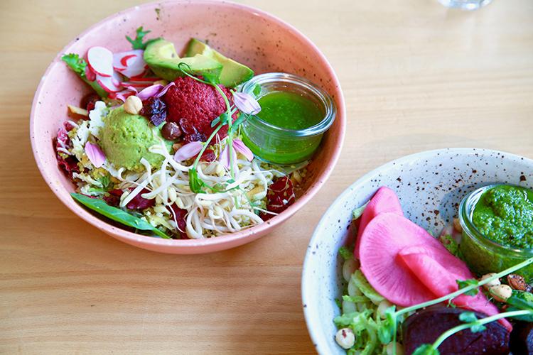 Vegansallad med ärthummus, rostade hasselnötter, hummus på säsongens beta, tranbär, avokado, quinoa och säsongens raw grönt i en skål på bord