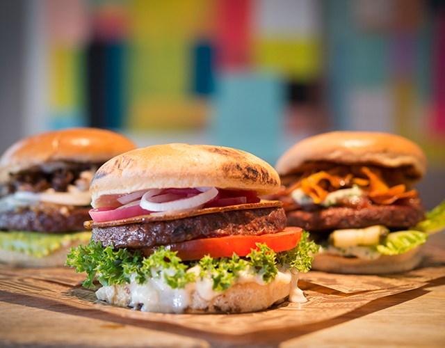 Tre hamburgare med bröd, sallad och grönsaker på ett uppläggningsfat