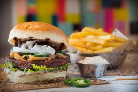 En hamburgare med bröd, sallad och grönsaker på ett uppläggningsfat,pommes i bakgrunden