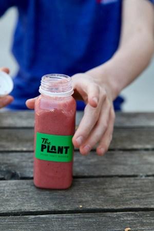 Röd smoothie i en plastflaska, en hand ska precis ta flaskan