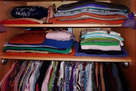 Garderob med kläder vikta på hyllor, under hänger kläder på galgar