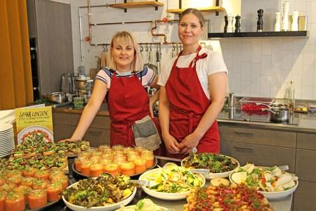 Två blonda kvinnor står vid ett buffébord