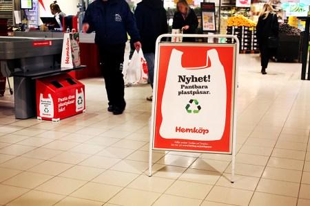 """En golvskylt vid butikskassa, på skylten en målad plastkasse i vitt med texten """"Nyhet! Pantbara plastpåsar"""" i svart"""