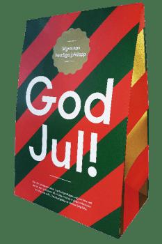 Presentförpackning i grönt och rött med texten God Jul! i vitt