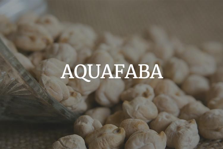 Kikärtor på ett bord från en vält skål med texten AQUAFABA