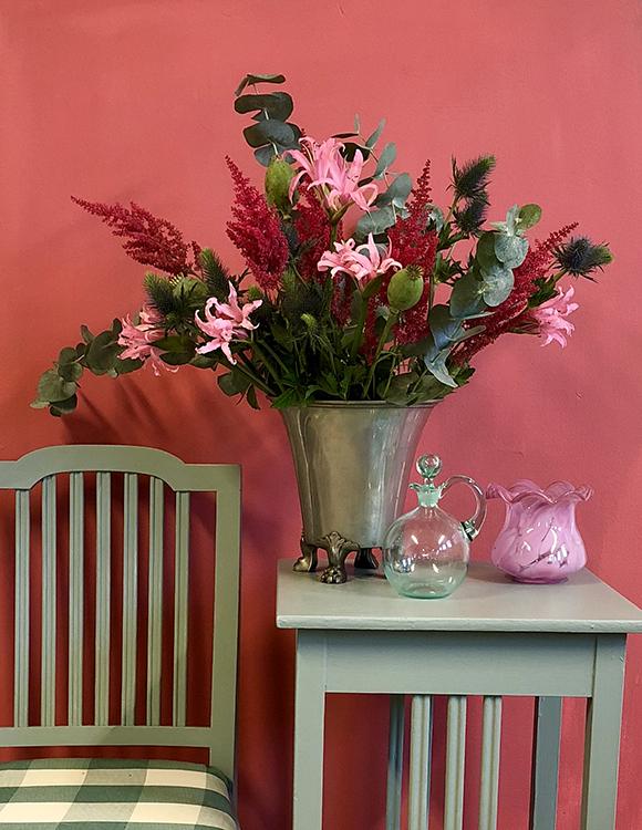 En stol och ett litet bord i mossgrönt. Bloomor i en vas på bordet