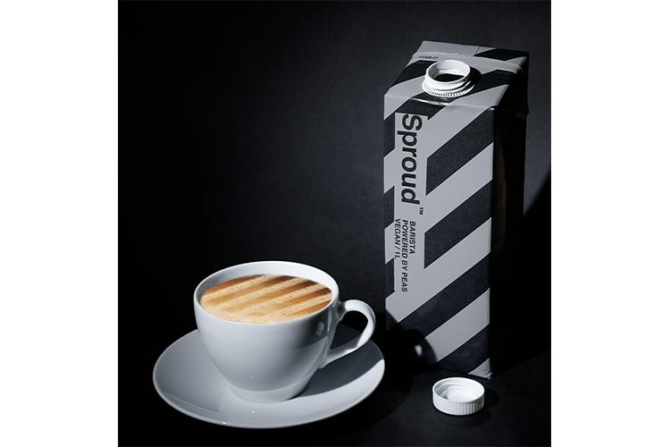 Kaffekopp med skummad mjölk, till höger en randig tetra med texten Sprud