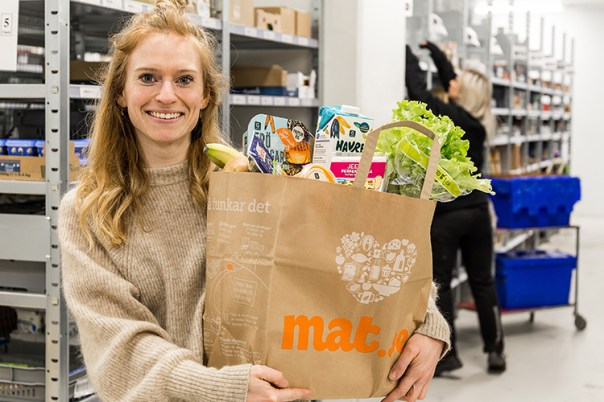 Kvinna med ljust långt hår håller i en brun papperskasse med matvaror. Texten mat.se på påsen.