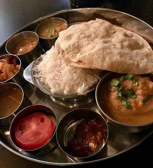 En rund silverbricka med små skålar med mat, i mitten ris och bröd