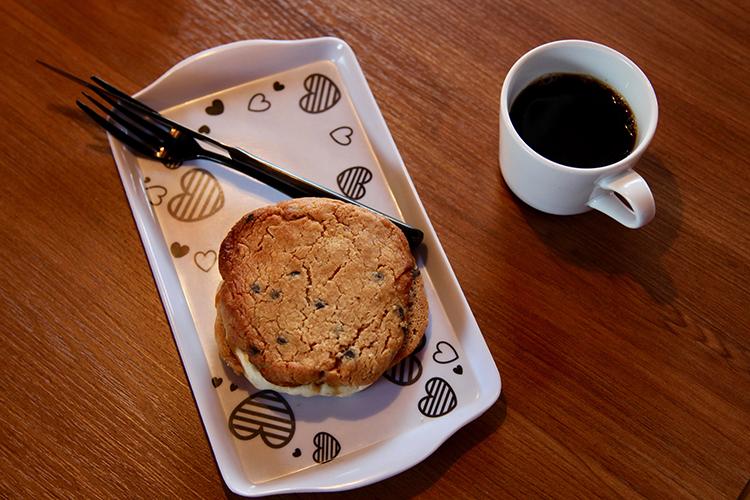 Ice creem & peanut butter cookie sandwich sedd uppifrån, en kopp kaffe till höger
