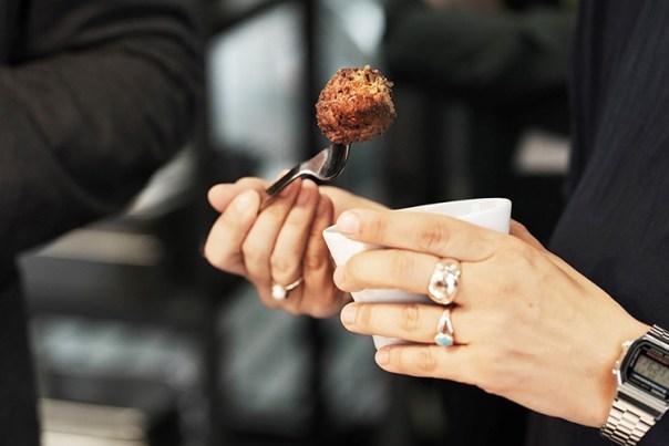 Händer med gaffel i den ena med en spetsad köttbulle