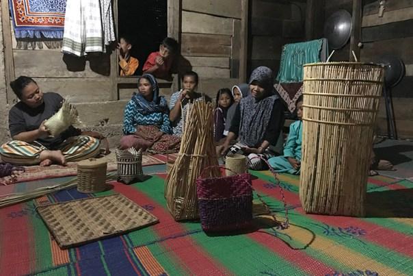 Flera kvinnor sitter på mattor med hantverk framför sig