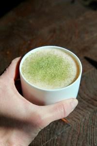 Vit dryck i vit mugg toppad med grönt pulver