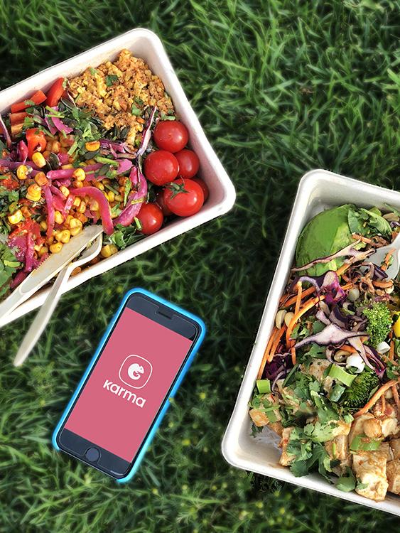 Två matboxar på gräs med en telefon med appen Karma mellan