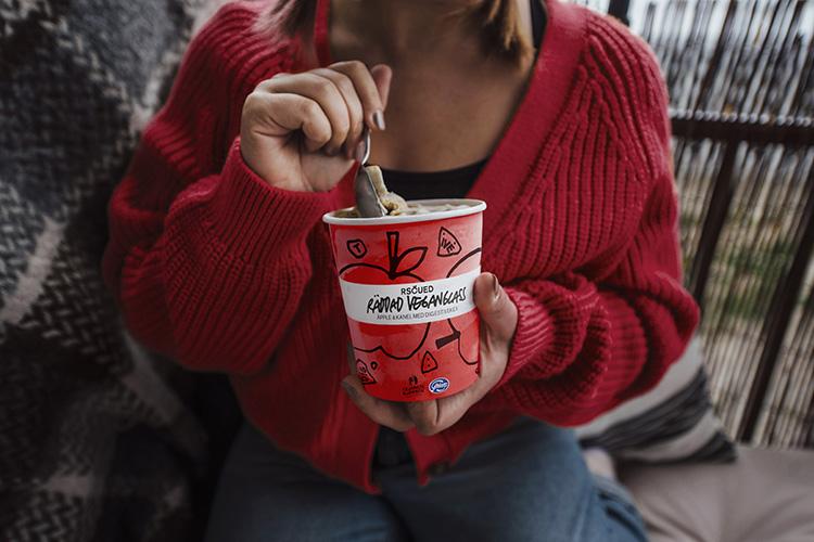 En person håller en glassbägare med en sked nedstucken i