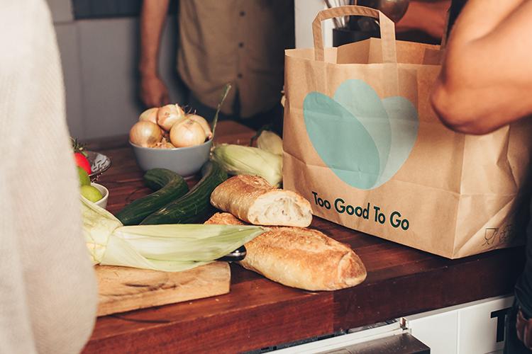 En bänk med bröd och grönsaker, bredvid en pappkasse med loggan Too Good To Go