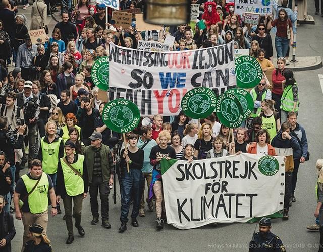 Strejkande personer med text Skolstrejk för klimatet