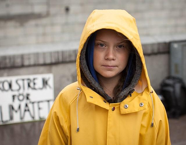 Greta i gul regnjacka, strejkskylt i bakgrunden