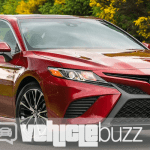 photograph of red 2018 Toyota Camry parked in front of trees.