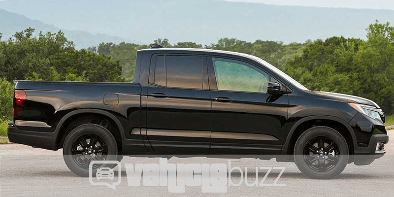 Sideview of black 2018 Honda Ridgeline parked in front of trees.