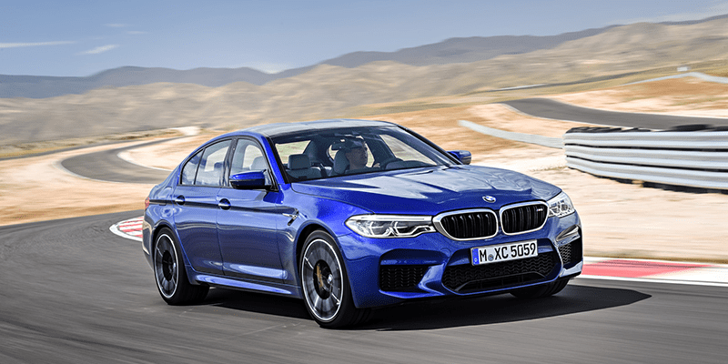 Front view of blue 2018 BMW M5 as it turns corner