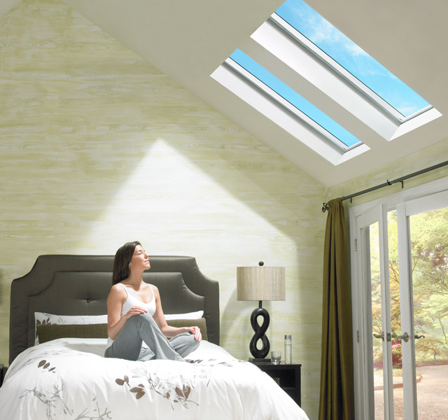 Woman enjoying the sunlight in her bedroom with velux fixed skylights also skylight curb mounted rh veluxusa