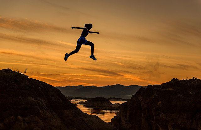 夕陽を背景に大きくジャンプする女性