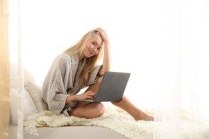 ベッドの上でノートPCをいじる女性