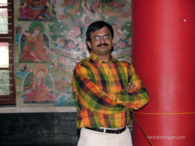 Behind me are tales from the life of Lord Buddha - Namdroling Monastery