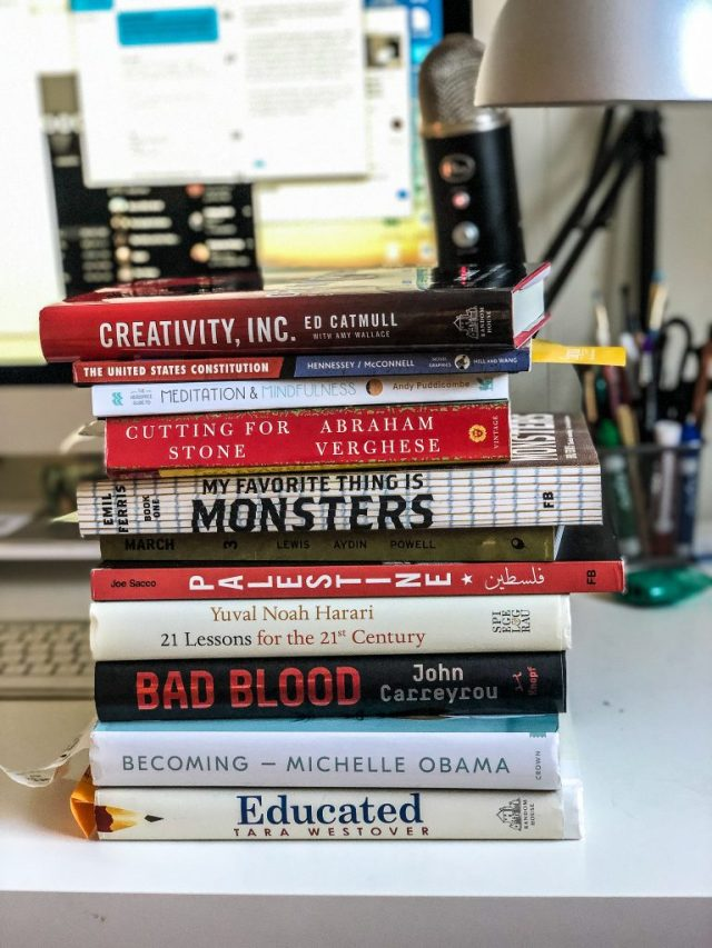 a stack of books resting on a desk.