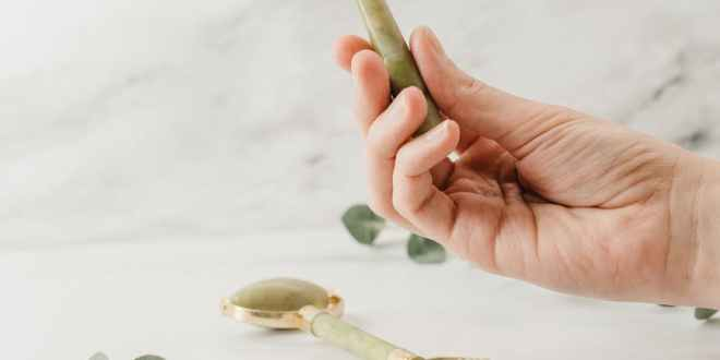 person holding silver spoon with white flower petals