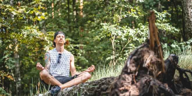man meditating on a tree log