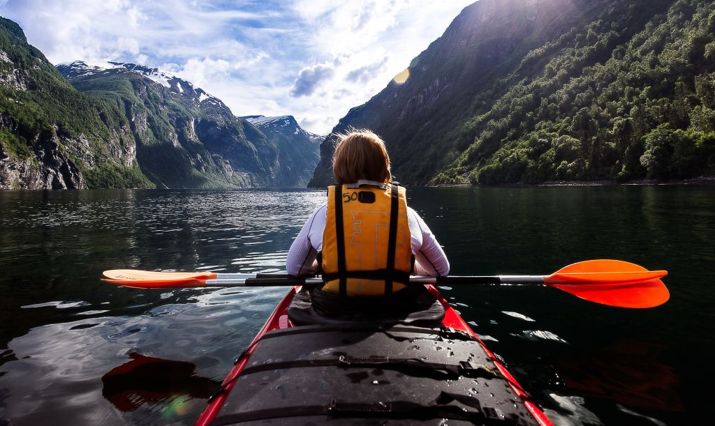 a teen on a kayak in the mountains