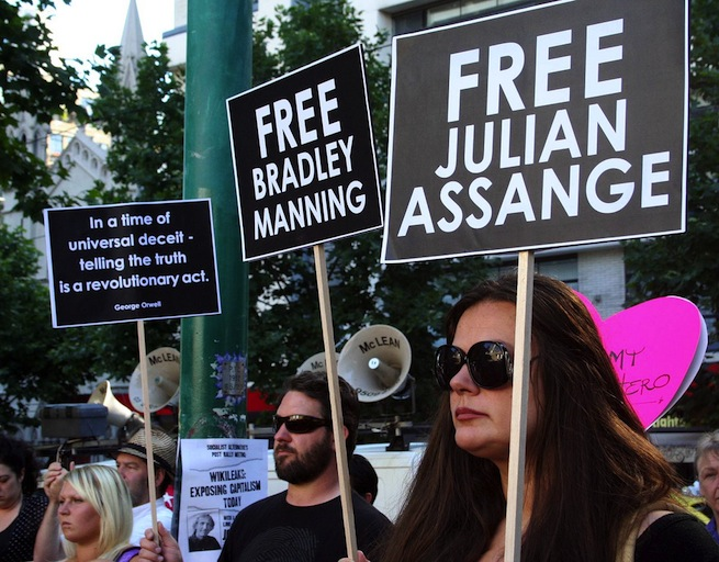"Protesters hold up ""free Julian Assange"" posters"